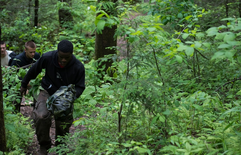Airman 1st Class Omari Whiteside, 4th Munitions Squadron precision guided munitions crewmember, leads a group of Airmen up the side of a mountain during combat survival training, near Brevard, North Carolina, May 21, 2020. The training consisted of learning land navigation, living off of the land, creating shelters, evading hostile enemies and more. (U.S. Air Force photo by Senior Airman Kenneth Boyton)