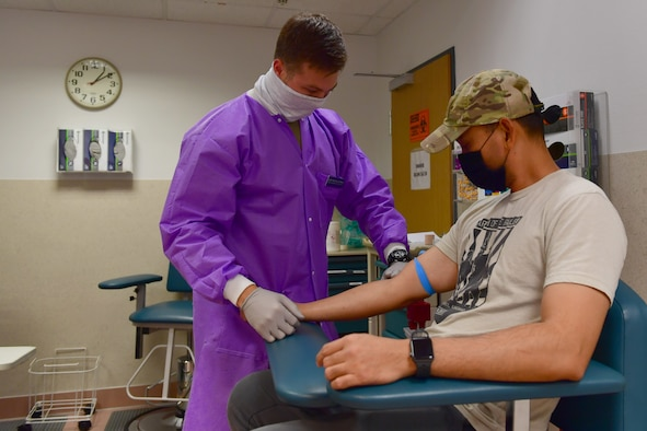 An Airman prepares a man's arm to take blood.