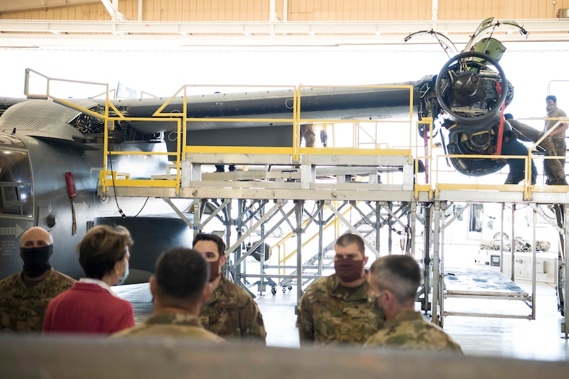Civilian woman speaks with airmen in a hangar while other airmen work on an aircraft in the background.
