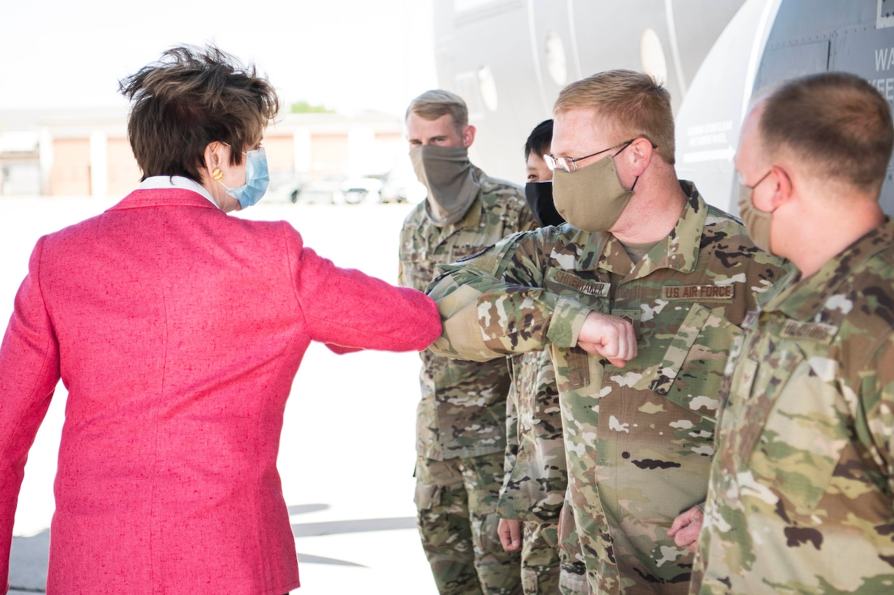 A civilian woman exchanges an elbow bump with one of several airmen she is meeting. All are wearing face masks.