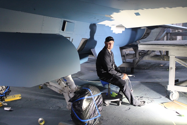 """576th Aircraft Maintenance Squadron paint shop technician, Jared Hart inspects an F-16 Fighting Falcon he helped paint with a """"ghost"""" paint scheme at Hill Air Force Base, Utah, May 21, 2020. The paint scheme is intended to replicate an adversary's fighter jet. United States, allied, and partner-nation aircrews routinely train against accurate and realistic threats including aircraft painted to replicate those pilots might see in aerial combat. (U.S. Air Force photo by Donovan Potter)"""