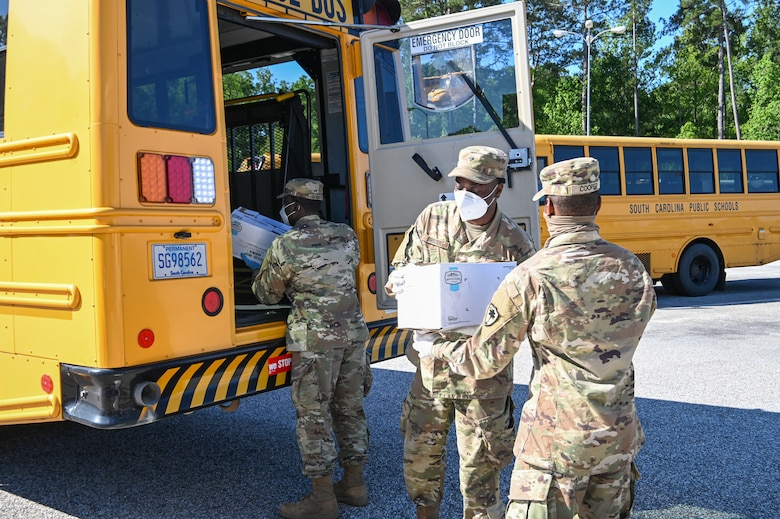 Soldiers load meals onto school buses for COVID-19 response