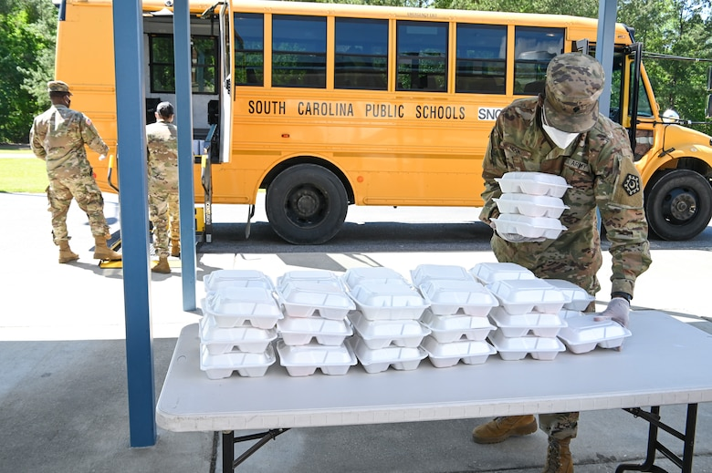 Soldiers load meals on school buses for COVID-19 response