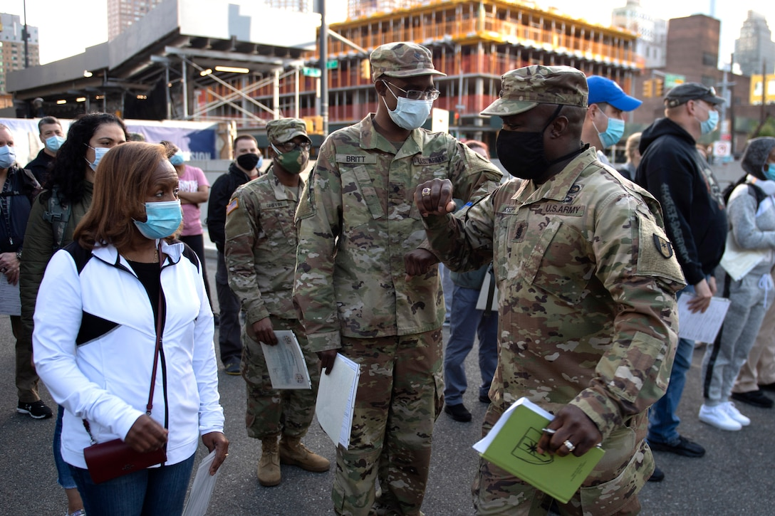 Soldiers wearing face masks stand outside in a large group of people.