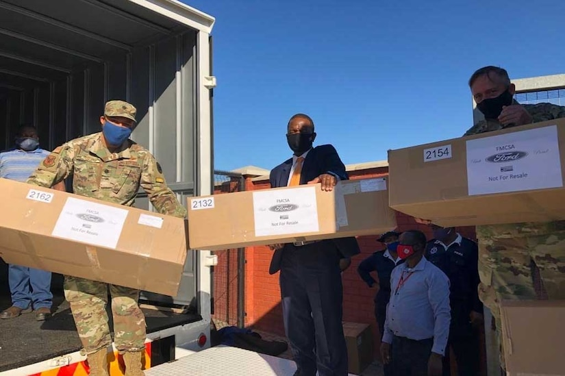 Two service members and a civilian carry cardboard boxes.