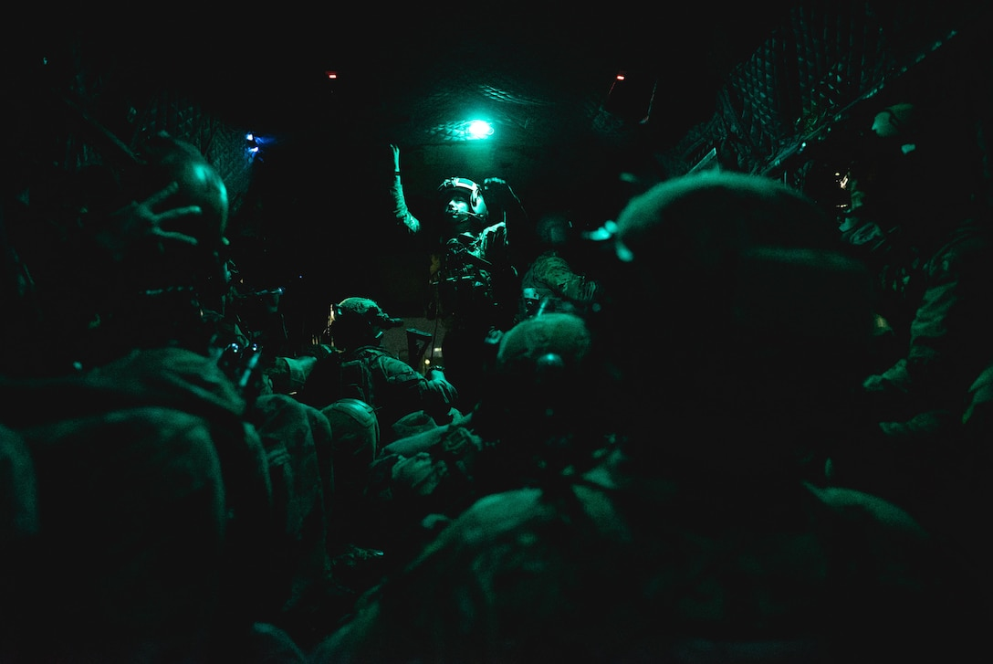 Multiple service members sit inside a vehicle.   They are illuminated by only a green light.