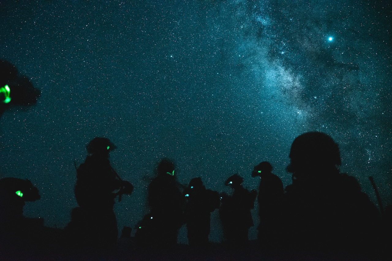 Multiple service members stand in silhouette before a star-illuminated night sky.