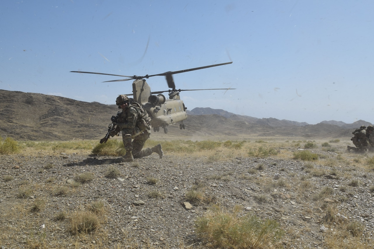 A soldier is on his knee on dusty terrain. Behind him, a CH-47 Chinook lifts off.