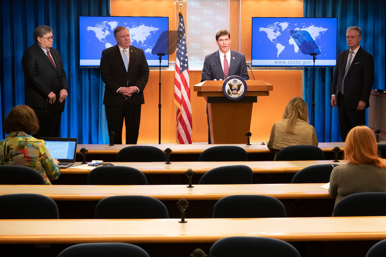 Defense Secretary Dr. Mark T. Esper speaks at a lectern as other leaders stand around him.