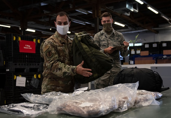 U.S. Air Force Tech Sgt. Mark Majack, left, 52nd Logistics Readiness Squadron section chief of personal property, passenger travel office, and Airman 1st Class Joshua Boozer, right, 52nd LRS Individual Protective Equipment apprentice, demonstrate putting a deployment bag together, June 4, 2020, at Spangdahlem Air Base, Germany. The 52nd LRS IPE Airmen are responsible for ensuring Airmen are properly equipped with gear needed for taskings, deployments, and temporary duty travel. (U.S. Air Force photo by Senior Airman Melody W. Howley)