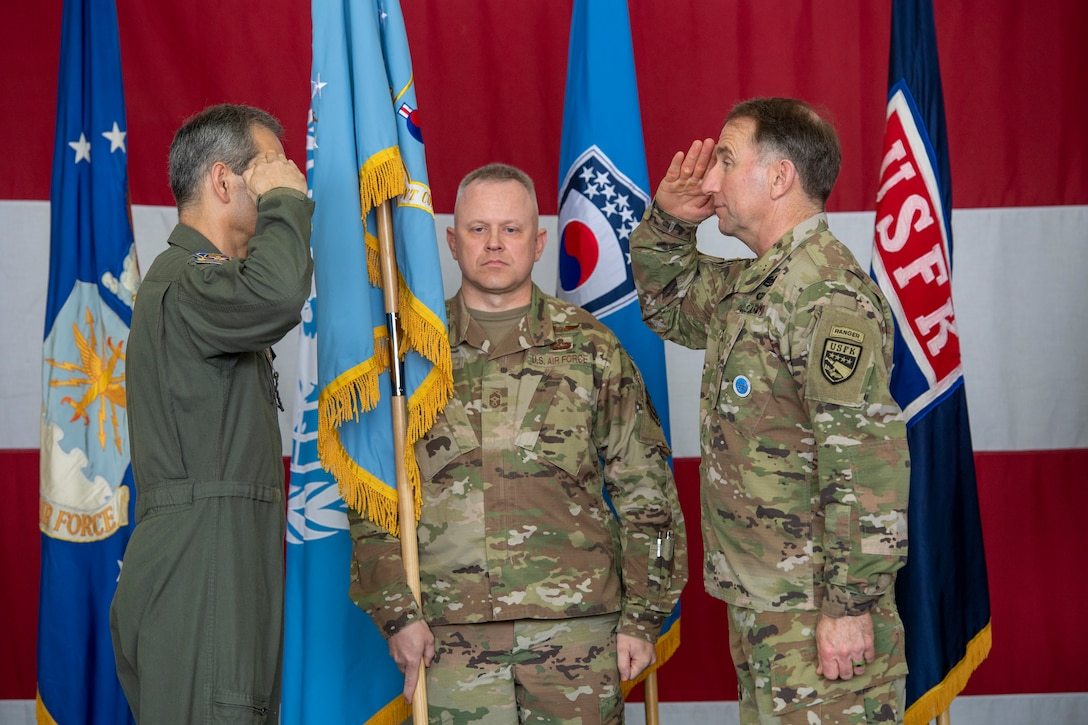 "Lt. Gen. Kenneth S. Wilsbach salutes Gen. Robert ""Abe"" Abrams, Commander, United Nations Command/Combined Forces Command/United States Forces Korea, as Chief Master Sgt. Philip Hudson, Seventh Air Force command chief holds a flag at Osan Air Base, ROK, June 12, 2020. Due to COVID-19 mitigation restriction, no official passing of the flag was conducted. (U.S. Air Force photo by Senior Airman Darien Perez)"