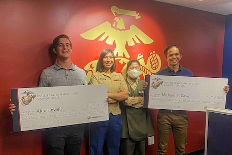 U.S. Marine Corps Staff Sgt. Maria Arzata, canvassing recruiter with Recruiting Station San Diego, and Capt. Katie Sliwoski, executive officer of Recruiting Station San Diego, present Alec Howell and Michael Cava the Naval Reserve Officers Training Corps scholarship in San Diego, Calif. on May 29, 2020. Howell and Cava graduated from Torrey Pines High School, applied, and won the scholarship together.