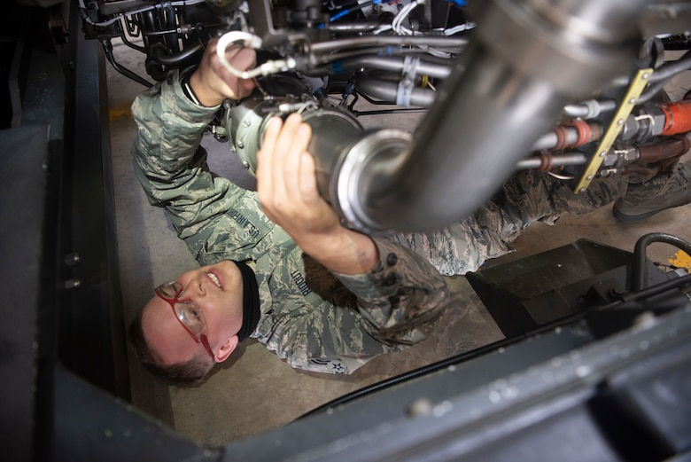 Airman 1st Class Eric Ridout, 100th Aircraft maintenance Squadron aerospace propulsion journeyman, examines the underside of an F108 turbofan engine at RAF Mildenhall, England, June 9, 2020. Jet propulsion Airmen are required to work in tight spaces to ensure the engines powering the 100th Air Refueling Wing's KC-135 fleet remain in good condition.  (U.S. Air Force photo by Airman 1st Class Joseph Barron)