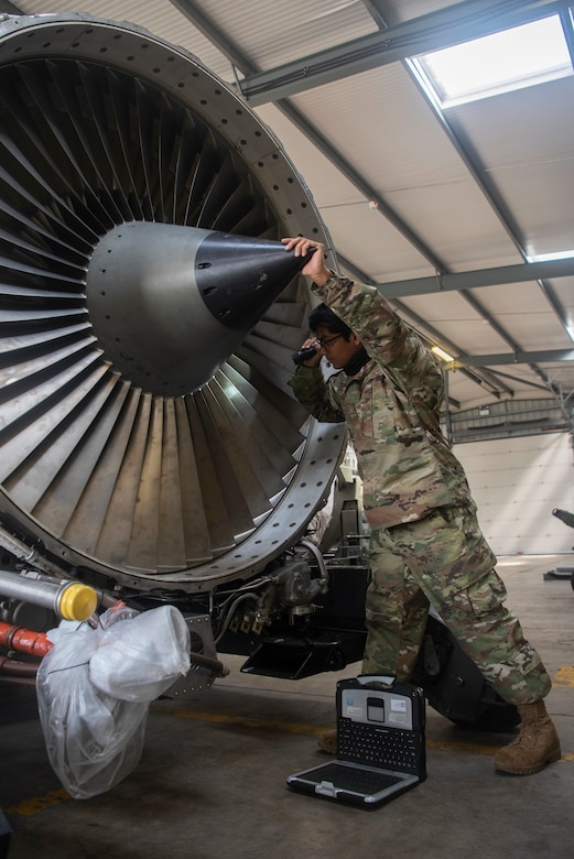 Airman 1st Class Rajendra Harilall, 100th Aircraft Maintenance Squadron aerospace propulsion journeyman, inspects the blades of an F108 turbofan engine at RAF Mildenhall, England, June 9, 2020. Maintainers frequently examine the blades for foreign object damage and to verify components can safely operate. (U.S. Air Force photo by Airman 1st Class Joseph Barron)