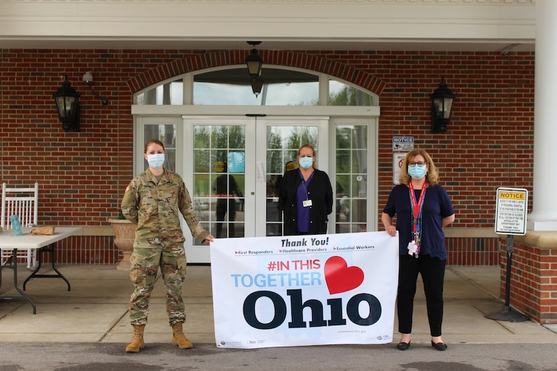 "Maj. Jessica Taylor (from left), commander of Company C, 237th Support Battalion, holds an ""#In This Together Ohio"" banner along with Ohio Veterans Home-Georgetown staff members Heather Doss, director of nursing, and Linda Slone, the facility administrator, at the Ohio Veterans Home in Georgetown, Ohio. In support of the Ohio Department of Veterans Services, Taylor recently led a team of Ohio National Guard medical personnel that conducted COVID-19 testing at the facility and also provided a supply of personal protective equipment. (Photo courtesy of Ohio Department of Veterans Services)"