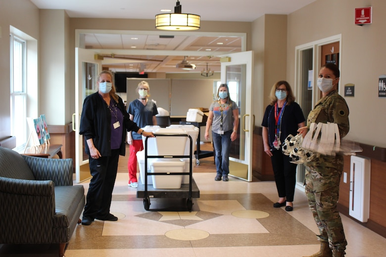 Maj. Jessica Taylor (right), commander of Company C, 237th Support Battalion, provides a supply of personal protective equipment to staff at the Ohio Veterans Home in Georgetown, Ohio. Taylor recently led a team of Ohio National Guard medical personnel that conducted COVID-19 testing at the facility, collecting samples from more than 200 staff members and approximately 140 resident veterans. (Photo courtesy of Ohio Department of Veterans Services)