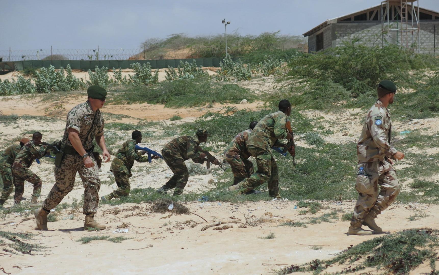 Instructors from the European Union Training Mission in Somalia (EUTM) take Somali National Army (SNA) soldiers through training drills at Jazeera Training Camp in Mogadishu. AMISOM (Raymond Baguma, 25 March 2015)