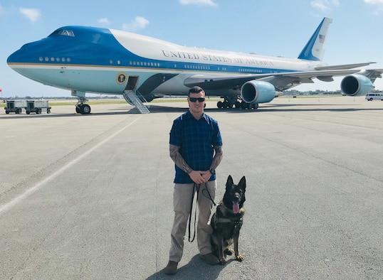 MAR-A-LAGO, Fla. – Staff Sgt. Danny Cohen, 21st Security Forces Squadron military working dog handler, and MWD Rexo, pose in front of Air Force One in Mar-A-Lago, Florida on Feb. 18, 2019. Cohen and Rexo were providing explosive detection for the United States presidential detail during their stay in Florida. (courtesy photo)