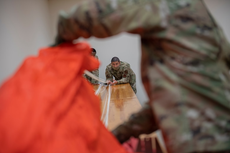 Aircrew Flight Equipment students work on a parachute