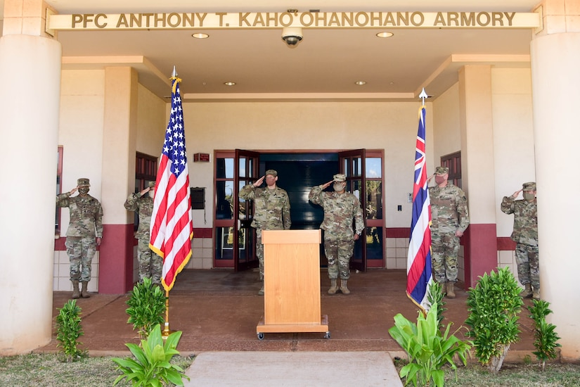 Six soldiers salute near a lectern at the entrance to a building.