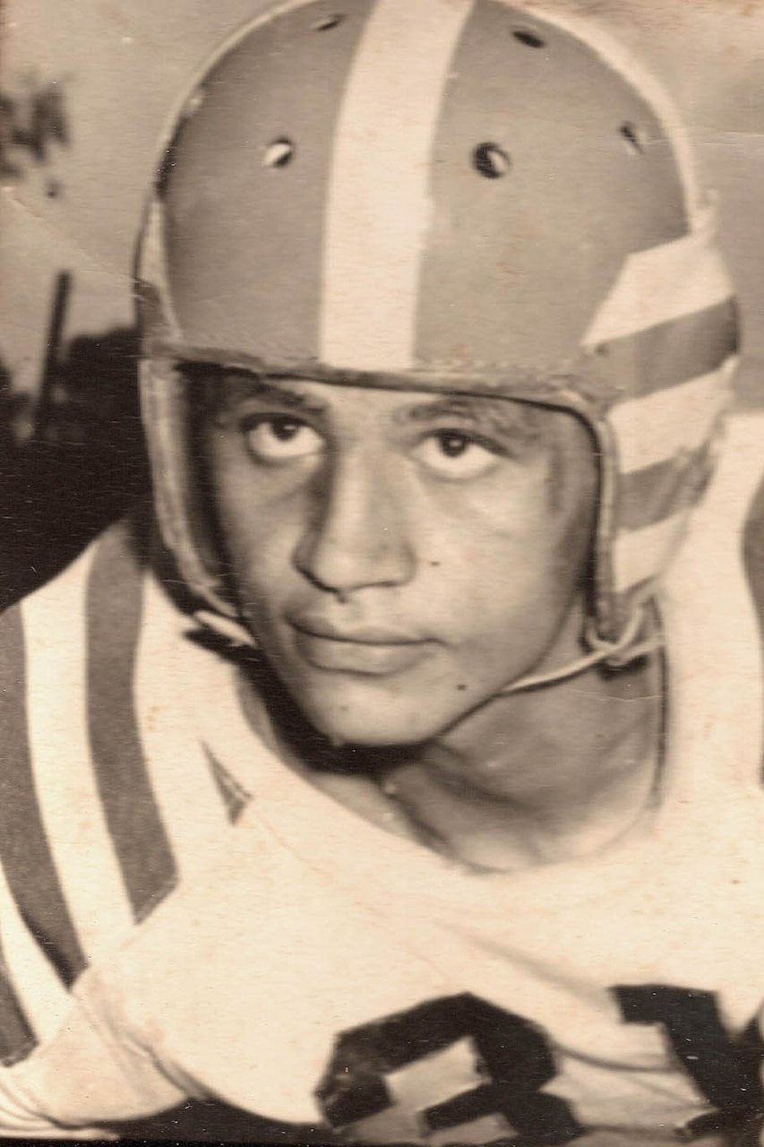 A young man wears a football helmet and jersey.