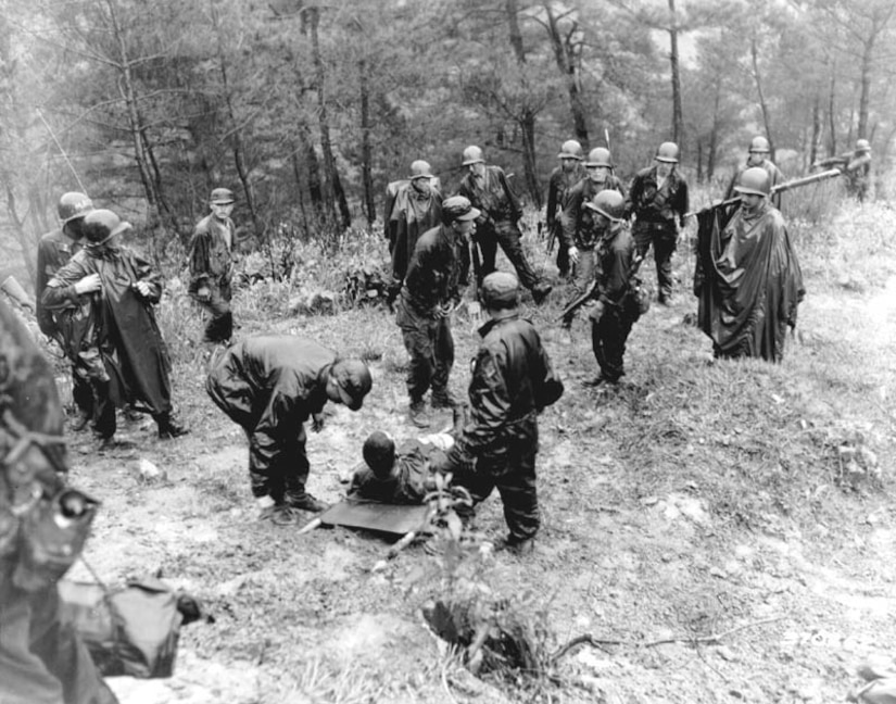 Several soldiers on a hill stand near a soldier on a stretcher.