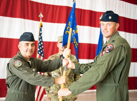 U.S. Air Force Col. Christian Kane, 325th Operations Group commander, left, awards command from U.S. Air Force Lt. Col. John Cummings, 325th Training Support Squadron commander, right, at Tyndall Air Force Base, Florida, on June 5, 2020. The 325th TRSS is responsible for conducting F-22 pilot academic and simulator training and F-15 flight simulators in support of air battle manager training. (U.S. Air Force photo by Airman Anabel Del Valle)