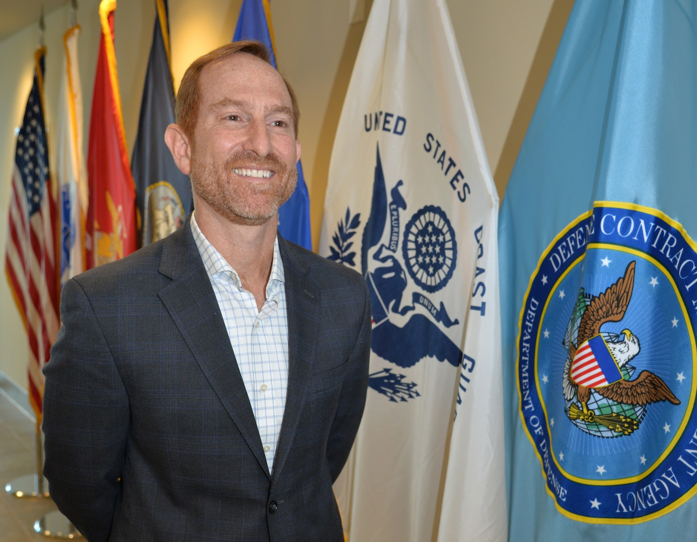 A smiling man stands beside a row of military flags