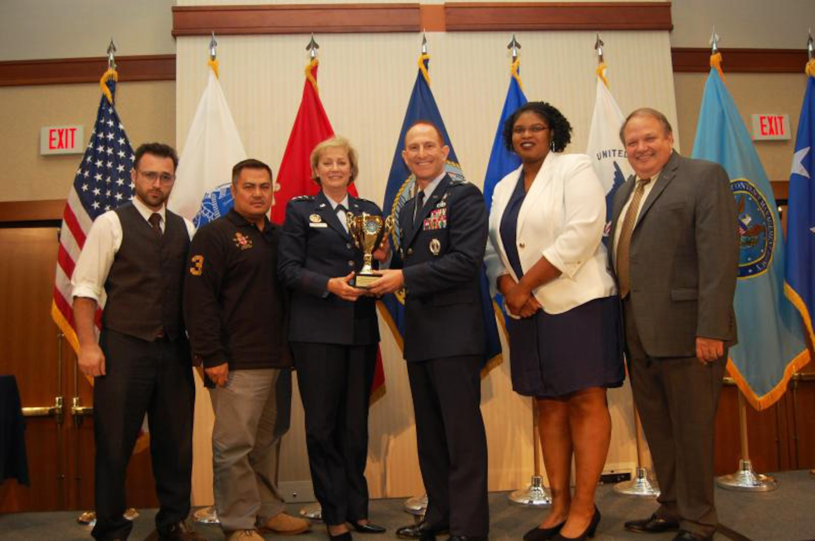 A group photo of military and civilian personnel smile while holding an award