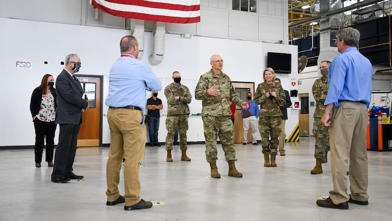 Gen. Bunch speaks with leadership standing in an aircraft maintenance hangar from the 309th Commodities Maintenance Group.