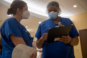 Air Force Capt. Lisbeth Whaley (left), an emergency trauma nurse with Urban Augmentation Medical Task Force 811-1, receives instructions before starting her shift at Stamford Hospital-Bennett Medical Center, Stamford, Conn., May 14, 2020. U.S. Northern Command, through U.S. Army North, remains committed to providing flexible Department of Defense support to the Federal Emergency Management Agency for the whole-of-nation COVID-19 Response. (U.S. Air Force photo by Senior Airman Nicholas Dutton)