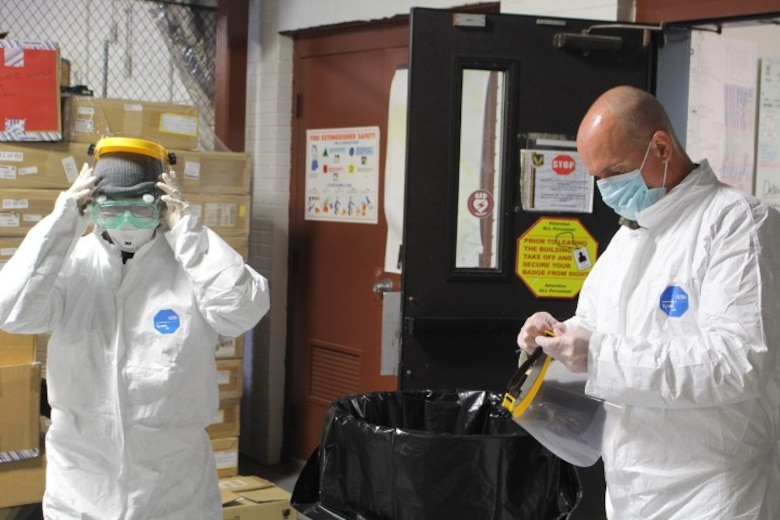 Members of the 480th Intelligence, Surveillance, and Reconnaissance Wing Emergency Management's cleaning team puts on their protective gear May 29, 2020 at Joint Base Langley-Eustis, Va. The EM team developed parameters and cleaning teams to perform trace cleanings to prevent any additional COVID-19 exposures within the building.