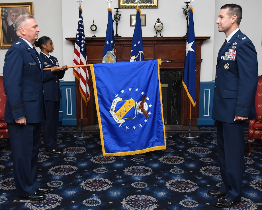 U.S. Air Force Chief Master Sgt. Christy Peterson, 11th Wing command chief, unfurls the 11th Wing flag while U.S. Air Force Maj. Gen. Ricky Rupp, Air Force District of Washington commander, and U.S. Air Force Col. Mike Zuhlsdorf, 11th Wing and Joint Base Anacostia-Bolling commander, stand at attention during the wing activation and assumption-of-command ceremony on Joint Base Anacostia-Bolling, Washington D.C., June 12, 2020. The 11th Wing -- The Chief's Own was activated on the base in preparation for assuming host-wing responsibilities. The base will officially transfer from Navy to Air Force responsibility in October 2020. (U.S. Air Force photo by 1st Lt. Kali Gradishar)