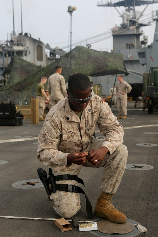 200610-M-CB805-1007 RED SEA (June 10, 2020) U.S. Marine Corps Staff Sgt. James Brooks, platoon sergeant, Weapons Platoon, Golf Company, Battalion Landing Team 2/8, 26th Marine Expeditionary Unit (MEU), loads a magazine prior to a pistol qualification range aboard the amphibious dock landing ship USS Oak Hill (LSD 51) June 10, 2020. Oak Hill with embarked 26th MEU is deployed to the U.S. 5th Fleet area of operations in support of naval operations to ensure maritime stability and security in the Central Region, connecting the Mediterranean and Pacific through the Western Indian Ocean and three critical chokepoints to the free flow of global commerce. (U.S. Marine Corps photo by Staff Sgt. Pablo D. Morrison)