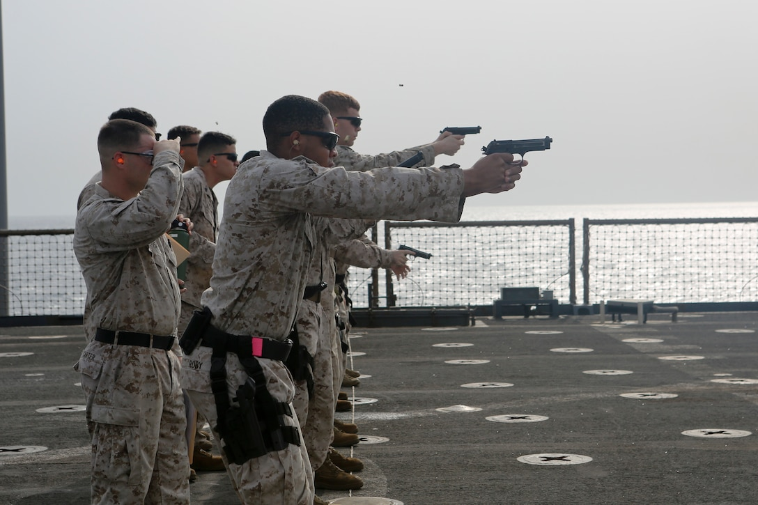 200610-M-CB805-1022 RED SEA (June 10, 2020) Marines assigned to the 26th Marine Expeditionary Unit (MEU) fire M9 pistols during a pistol qualification range aboard the amphibious dock landing ship USS Oak Hill (LSD 51) June 10, 2020. Oak Hill with embarked 26th MEU is deployed to the U.S. 5th Fleet area of operations in support of naval operations to ensure maritime stability and security in the Central Region, connecting the Mediterranean and Pacific through the Western Indian Ocean and three critical chokepoints to the free flow of global commerce. (U.S. Marine Corps photo by Staff Sgt. Pablo D. Morrison)