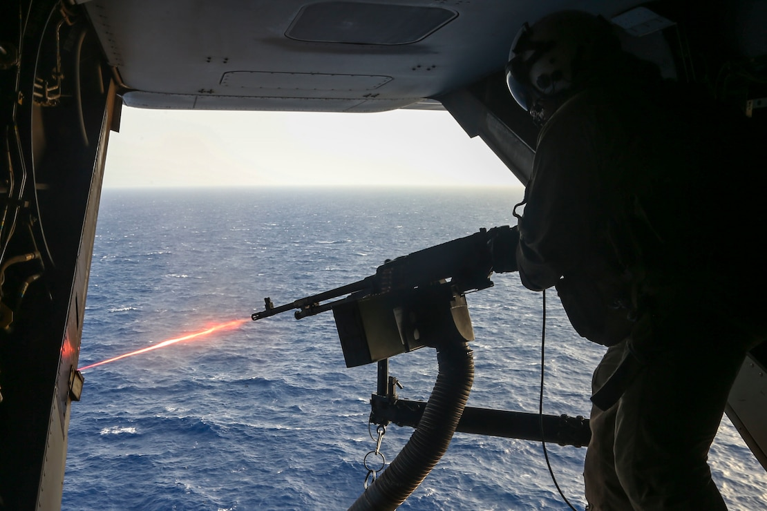 200606-M-KE756-1023 ARABIAN SEA (June 6, 2020) Sgt. Cullen McNeil, crew chief, assigned to Marine Medium Tiltrotor Squadron (VMM) 365 (reinforced), 26th Marine Expeditionary Unit (MEU), fires an M240B machine gun from an MV-22B Osprey June 6, 2020. 26th MEU is deployed to the U.S. 5th Fleet area of operations in support of naval operations to ensure maritime stability and security in the Central Region, connecting the Mediterranean and Pacific through the Western Indian Ocean and three critical chokepoints to the free flow of global commerce. (U.S. Marine Corps photo by Cpl. Tanner Seims)
