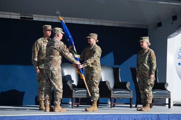 Lt. Gen. Brad Webb, the Air Education and Training Command commander, passes the 502d Air Base Wing colors to Brig. Gen. Caroline Miller, the newest commander of the wing and Joint Base San Antonio during a modified ceremony June 12 at JBSA-Fort Sam Houston, Texas.