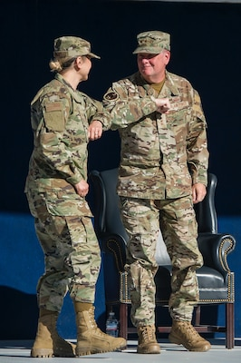 """Brig. Gen. Caroline Miller, (left) the incoming commander for the 502d Air Base Wing and Joint Base San Antonio, bumps elbows with Lt. Gen. Marshall """"Brad"""" Webb, the Air Education and Training Command commander, during a change of command ceremony June 12 at JBSA-Fort Sam Houston."""