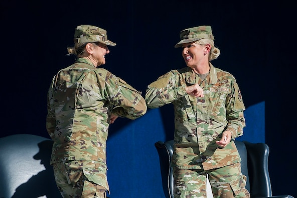 Brig. Gen. Caroline Miller, left, bumps elbows with Brig. Gen. Laura Lenderman during the 502d Air Base Wing and Joint Base San Antonio change of command ceremony June 12 at JBSA-Fort Sam Houston, Texas. Command of the unit passed from Lenderman to Miller during the ceremony.
