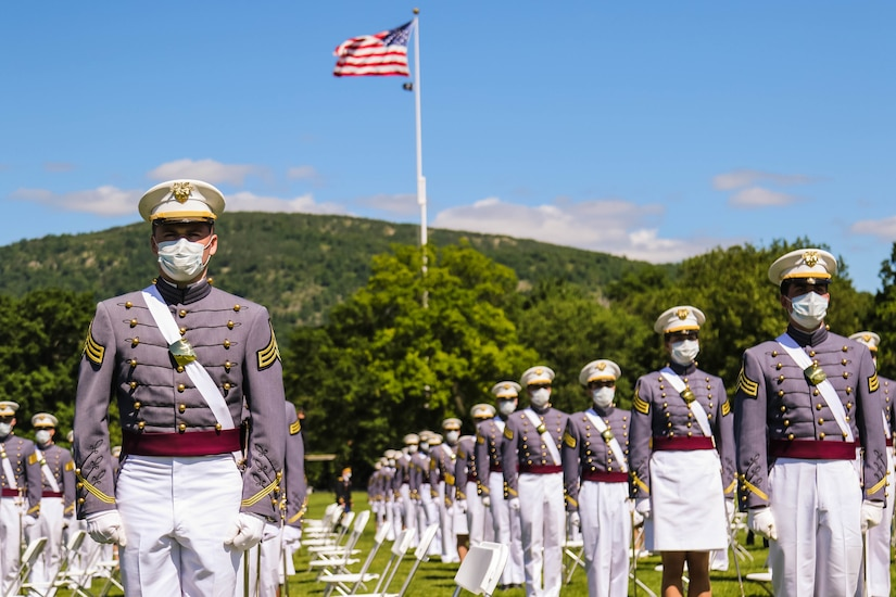 Cadets stand in formation as an American flag flutters above them.