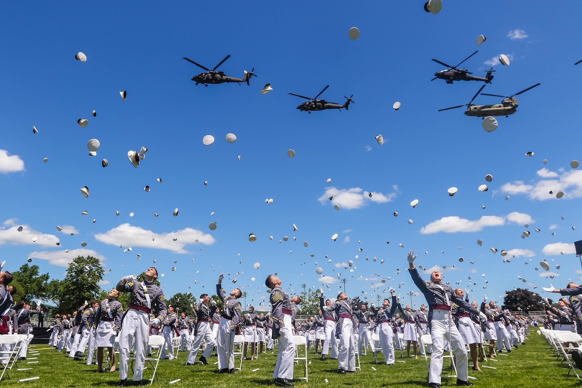 Cadets throw their hats in the air as a group of helicopters fly above them.