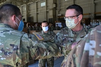 Sgt. Andrew Stock, Headquarters and Service Company, 3643d Brigade Support Battalion, bumps elbows with Gen. Joseph Lengyel, Chief of the National Guard Bureau, at the New Hampshire National Guard Army Aviation Support Facility warehouse on May 27, 2020, in Concord.