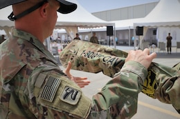 Cmd. Sgt. Maj. John Hurt of the 1st Squadron, 303rd Cavalry Regiment (1-303 CAV), cases his unit's colors during the transfer of authority ceremony