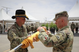 Lt. Col. Timothy Ozmer (right), Commander of the 1st Squadron, 303rd Cavalry Regiment (1-303 CAV), and Cmd. Sgt. Maj. John Hurt (left), case their unit colors during the transfer of authority ceremony