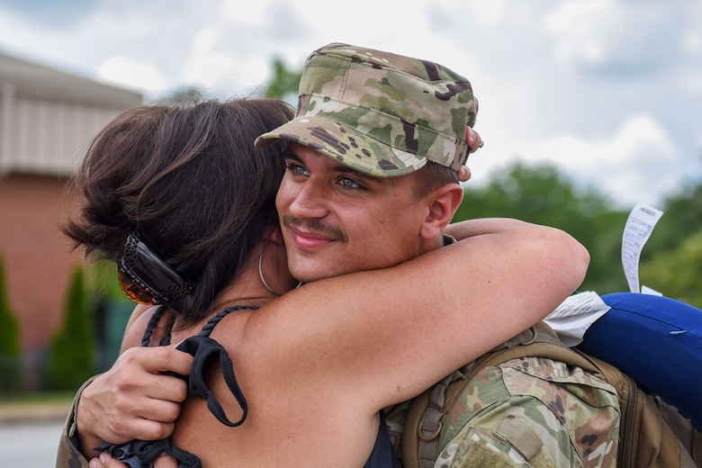 Photo of a service member smiling as a family member hugs him.