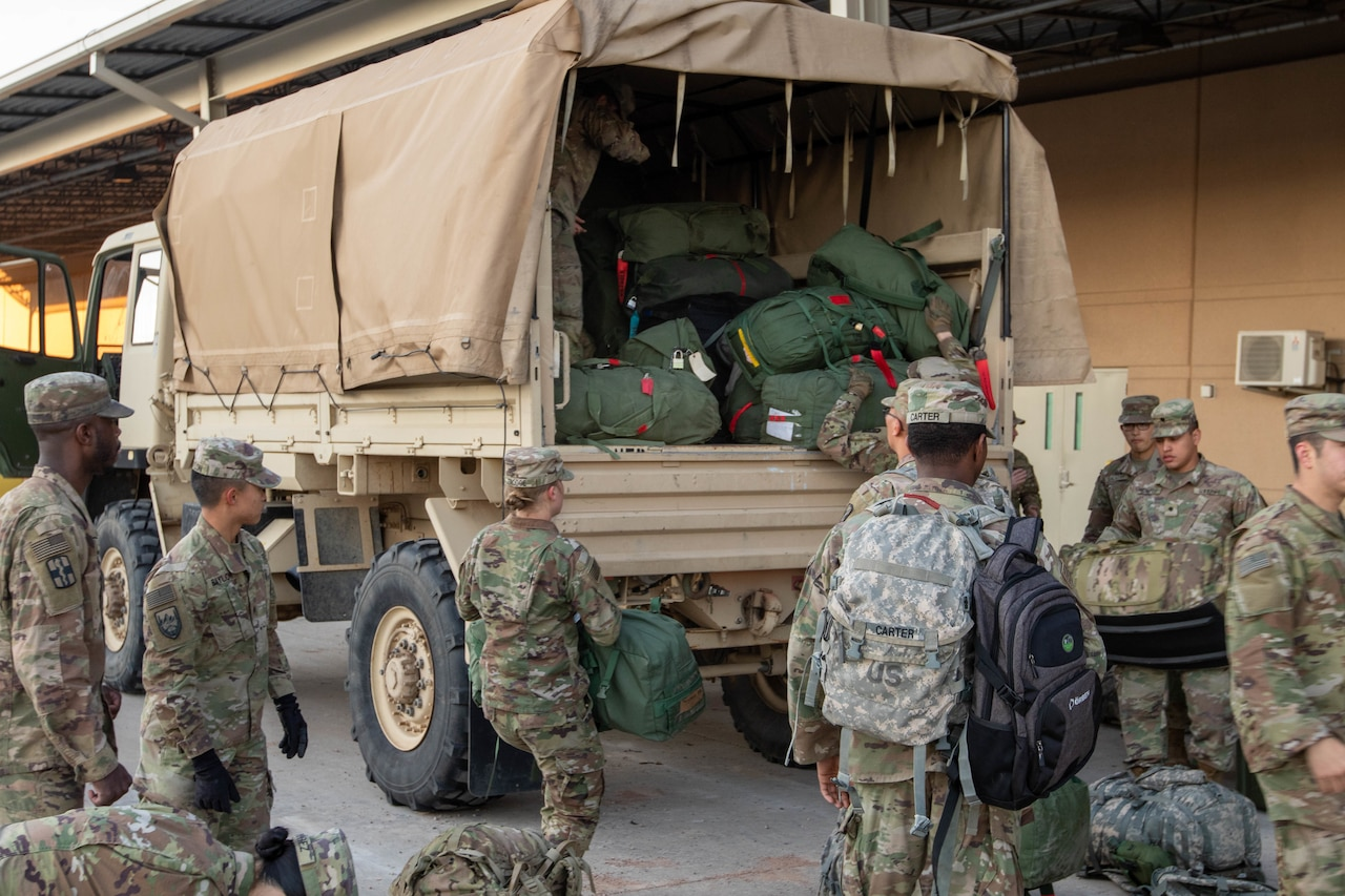 Soldiers pack gear into a military truck.