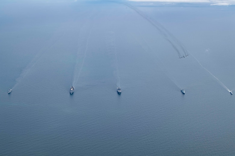 aircraft flying over five ships