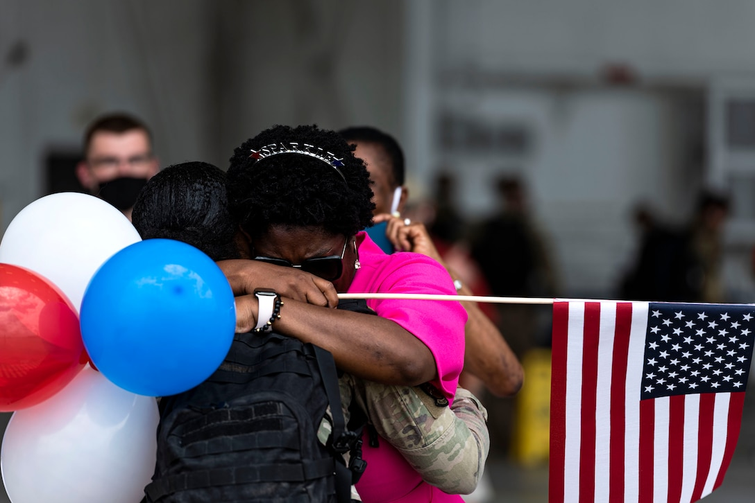 Photo of Airman hugging their family.