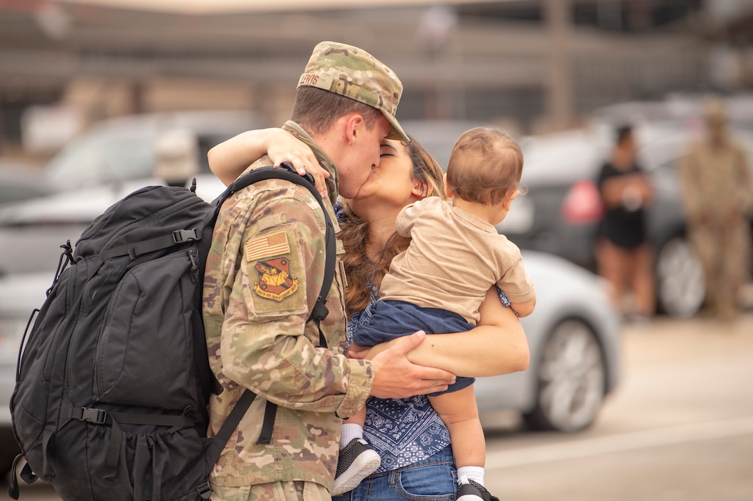 An Airman assigned to the 74th Expeditionary Fighter Squadron embraces his family after a 5-month deployment June 10, 2020, at Moody Air Force Base, Georgia. Approximately 300 members assigned to the 74th EFS returned from deployment June 10-12. The 74th EFS, which consisted of personnel from the 23d Fighter Group and 23d Maintenance Group, were deployed as a part of Operation Freedom Sentinel. (U.S. Air Force photo by 2nd Lt. Kaylin P. Hankerson)