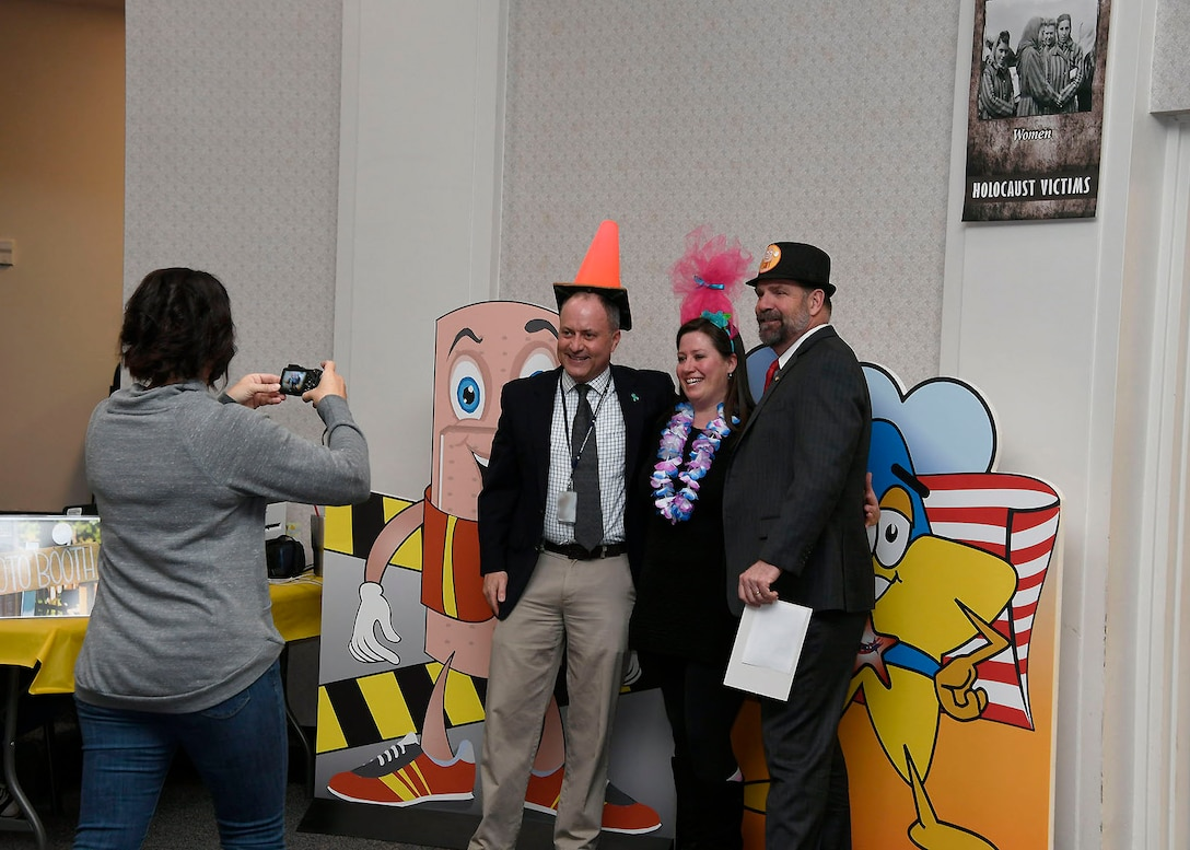 Don Phillips, left, director for DLA Installation Management at Battle Creek, Michigan, and DLA Disposition Services Director Mike Cannon, right, have some fun with Voluntary Protection Program team member Lyndi Brown at the 2019 Spring Into Safety photo booth.